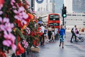 Unidentified people walking on a street in London, UK, blossoming flowers.
